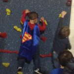 Young boy climbing rock wall with superhero cape on.