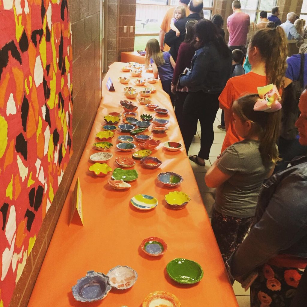 people waiting to view and purchase empty ceramic bowls created by students for empty bowl fundraiser