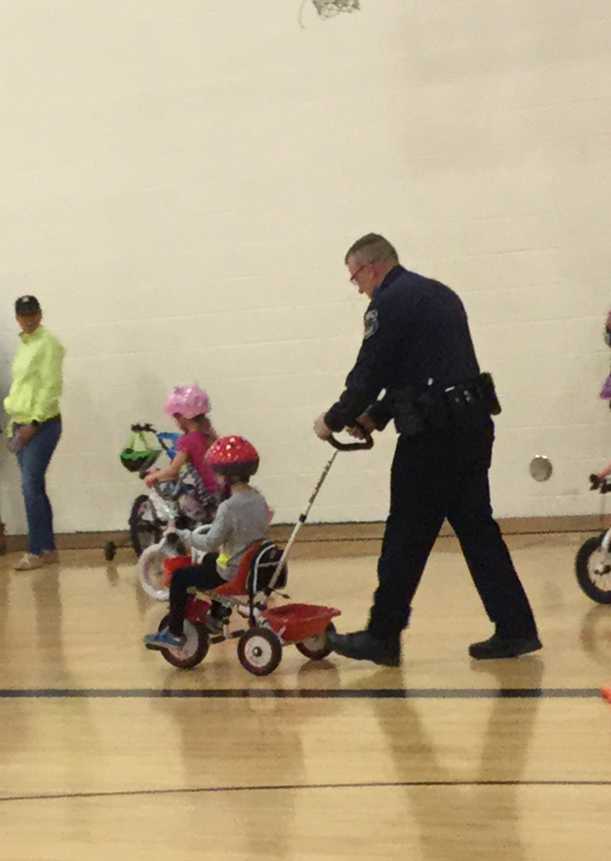 Officer Cole pushing a child on a tricycle during the bike-a-thon